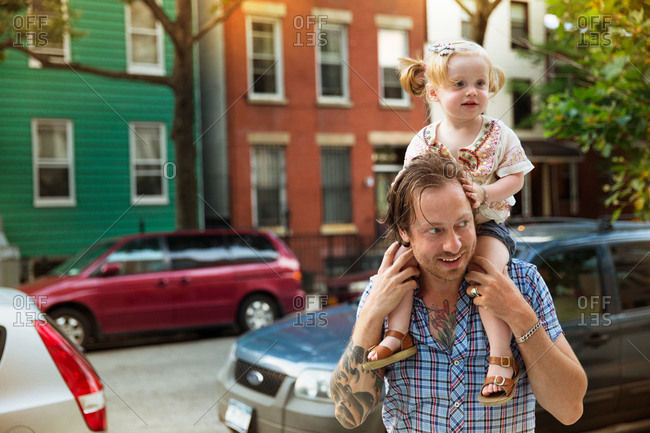 A little girls sits on her father's shoulders
