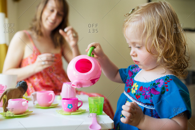 Mother and daughter play with a teaset