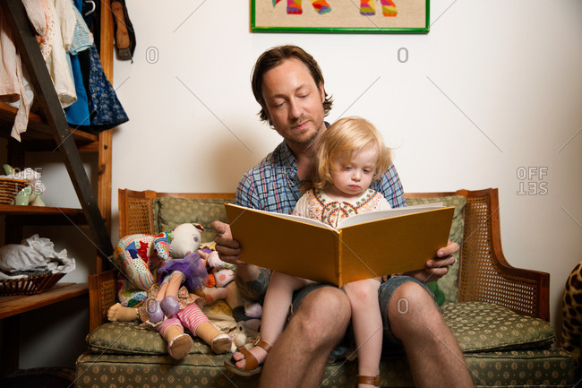 A father reads a book to his daughter