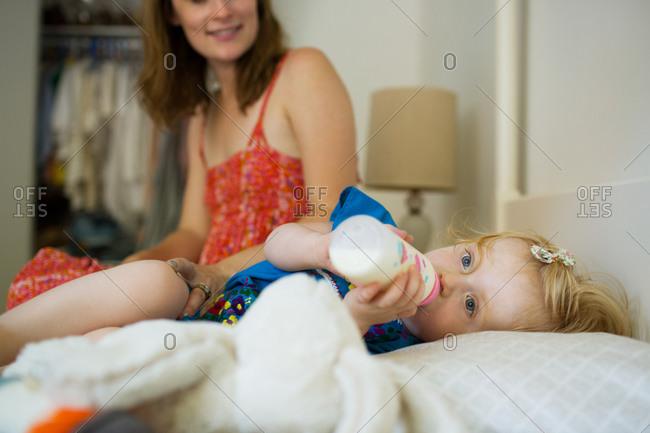 Little girl drinking milk from a bottle
