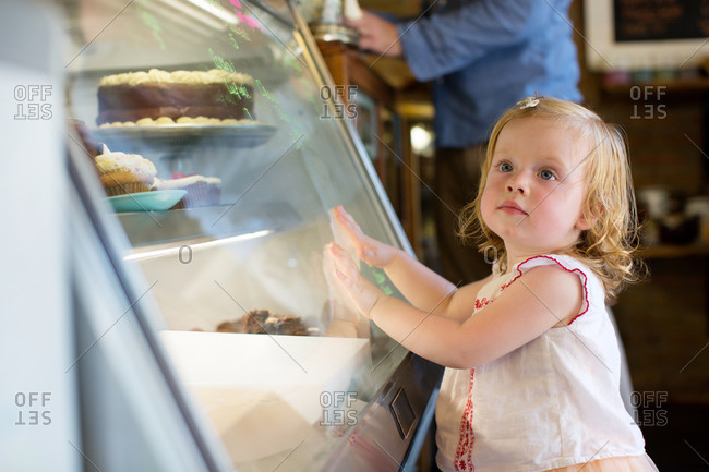A little girl stands in pastry shop
