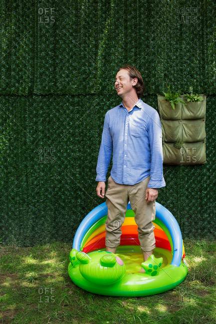 Man standing in inflatable baby pool