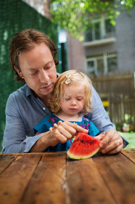 Father and daughter examining a slice of watermelon