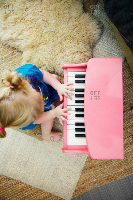 Little girl playing with toy piano