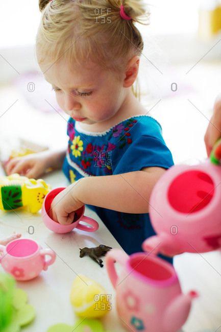 Little girl playing with miniature tea set
