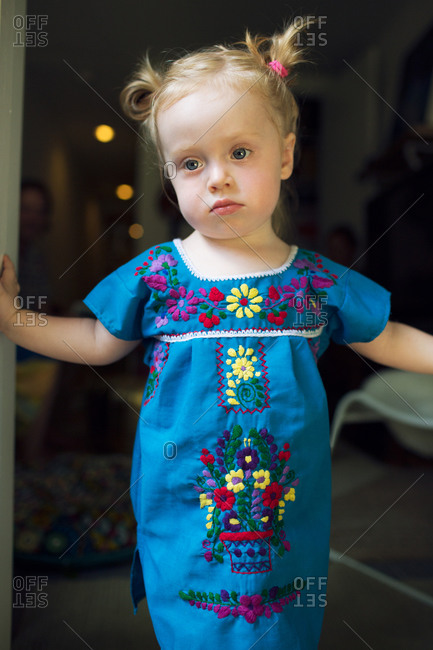 Little girl in embroidered dress standing in doorway