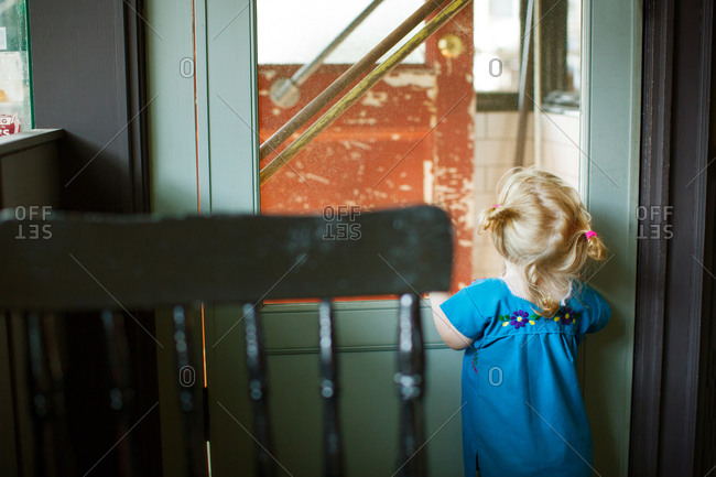 Rear view of little girl peeking out of a screen door