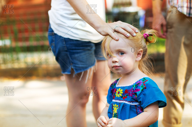 A mother tousles her daughter's hair