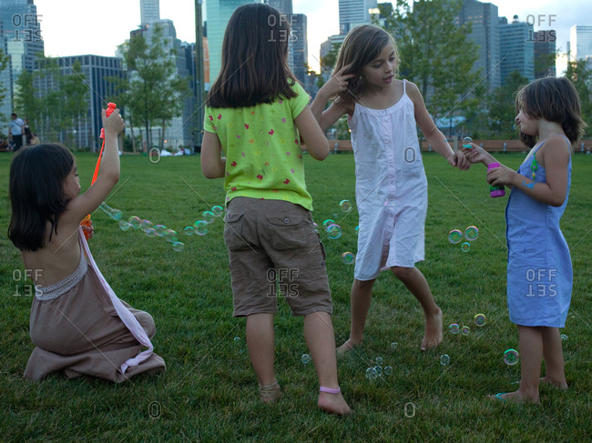 Little girls playing with soap bubbles.