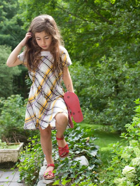 Little girl walking on stone parapet.