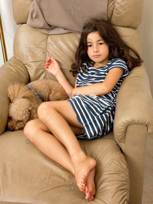 Young girl resting in leather armchair with her pet.