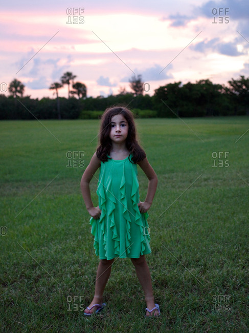 Young girl standing in straddle position on green field.