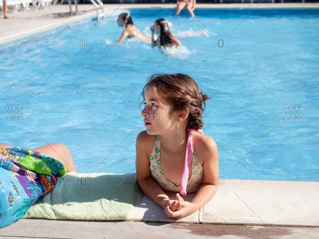 Young girl at the side of a swimming pool