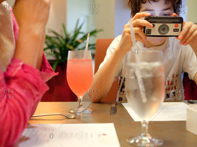 A young boy playing with his cell phone at a restaurant