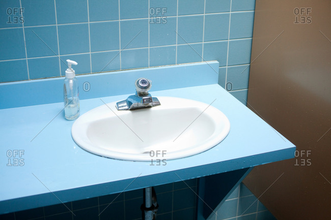 A white ceramic washing sink on a blue tiled wall