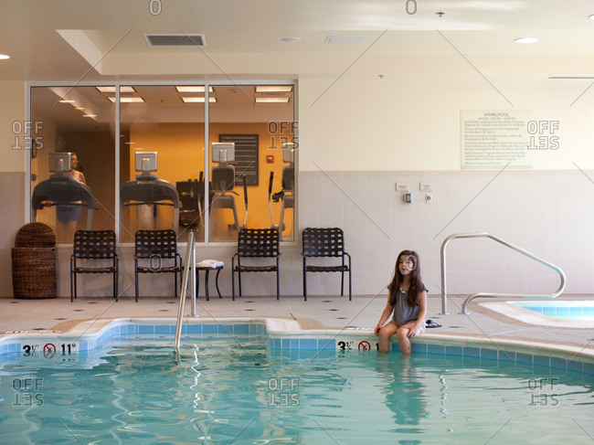 A young girl sitting by the side of a public swimming pool
