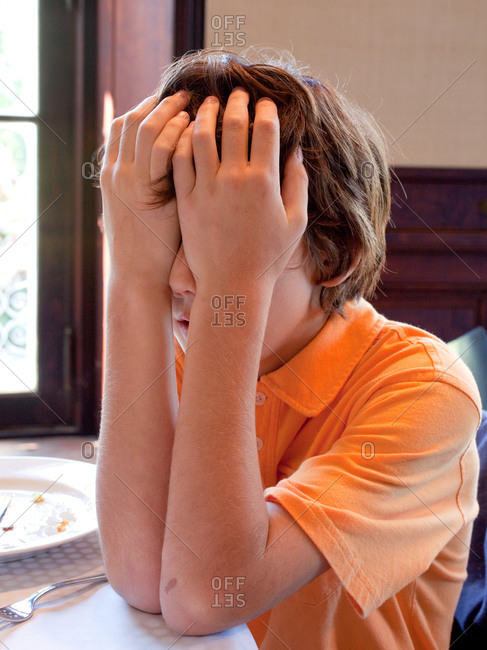 A young boy at the dinner table with his hands covering his face