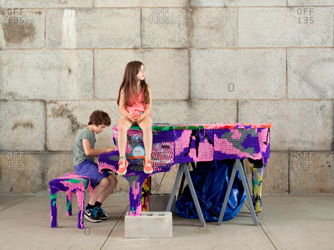 A young boy and girl sitting on a retro, cover wool knitted, piano