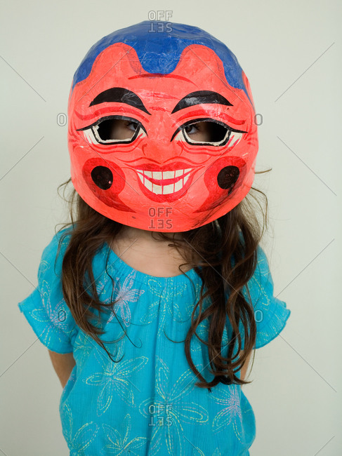A young girl wearing a costume mask