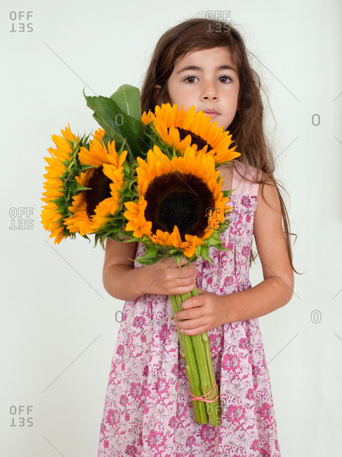 Portrait of young girl holding sunflowers