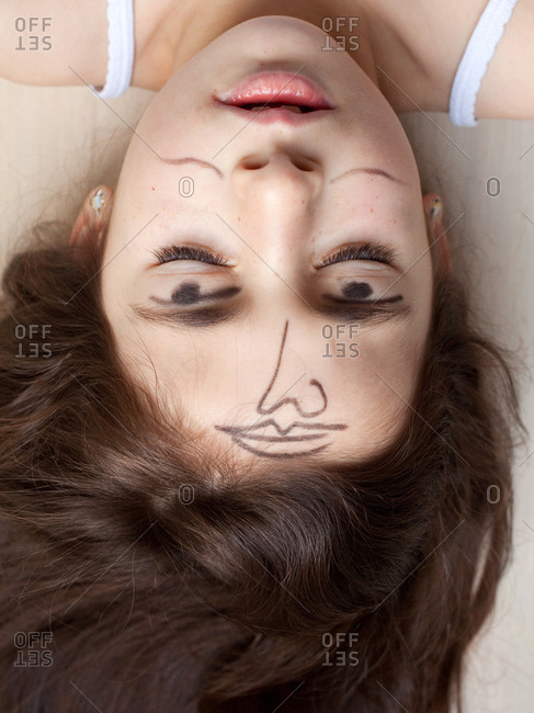 Upside down portrait of young girl with face doodling