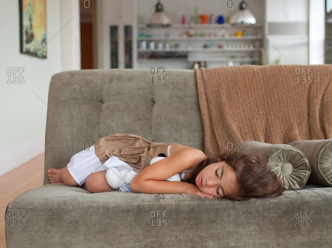 Young girl sleeping on sofa with plush toy