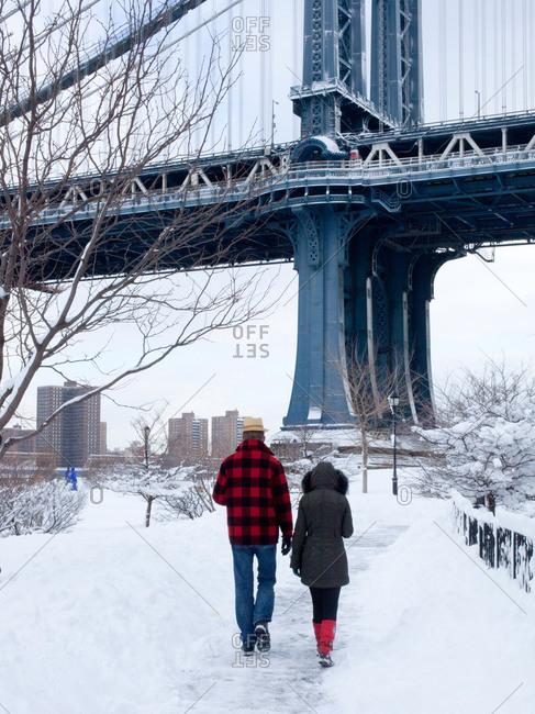 Rear view of couple walking on riverside in winter