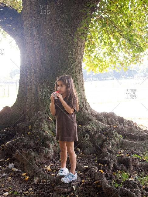 Young girl eating flavored ice under tree