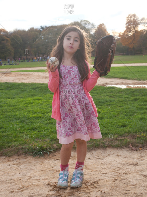 Young girl standing with baseball and glove