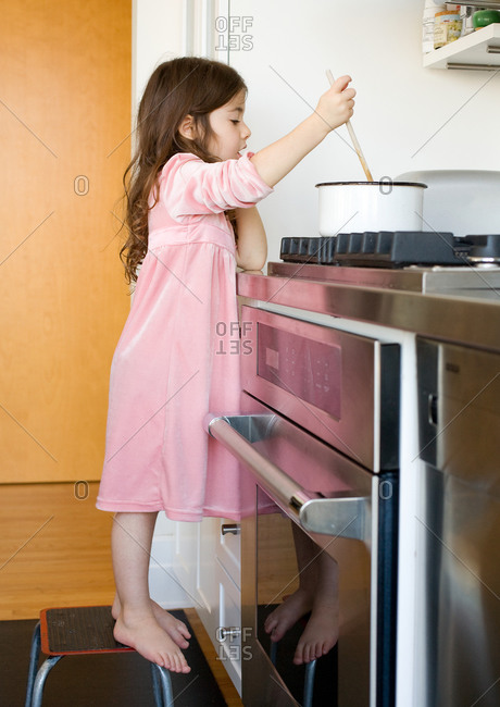 Young girl standing on chair in kitchen and stirring food in pot