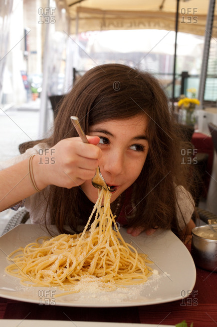 Young girl eating pasta with cheese