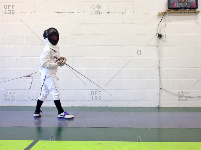 Young epee fencer standing on piste