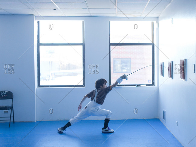 Young boy practicing point control in fencing room