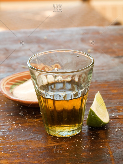 Shot glass of tequila with lime and salt