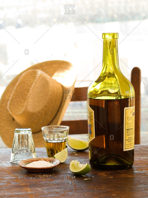 Bottle of tequila, shot glasses, lime slices and salt on table