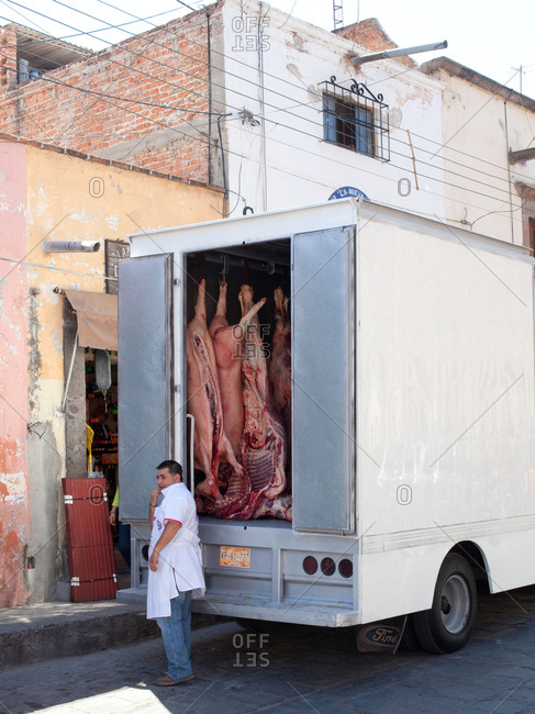 Butcher standing next to refrigerator truck on the street