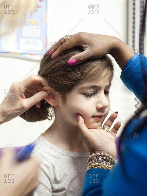 Close up of young girl being pierced