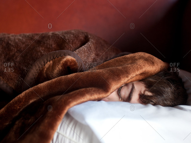 Close up of young boy sleeping with face covered with blanket