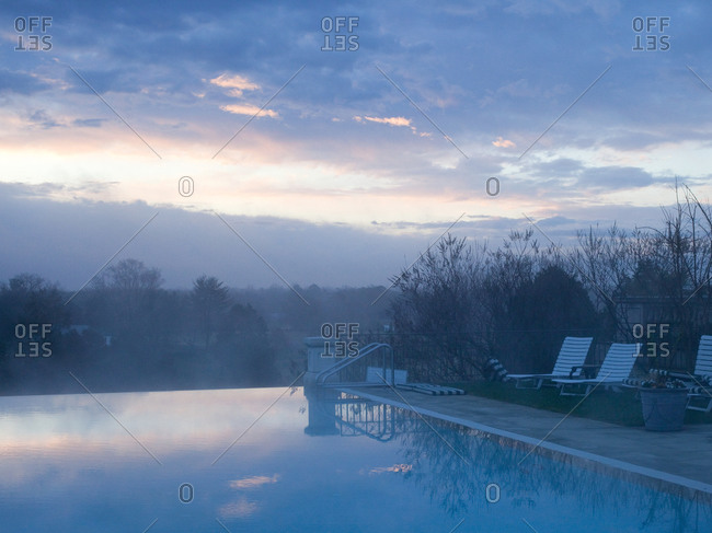 Infinity pool with lounge chairs at dawn