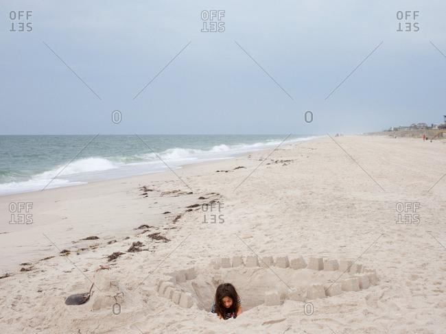 Young girl on a sandy beach building sand castle