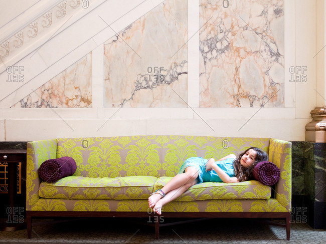 Young girl laying on a sofa