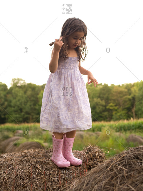Young girl standing on a hay bale