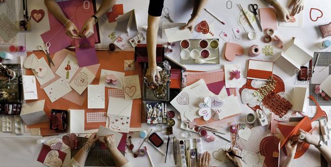 Top view of women making greeting cards for Valentine's day
