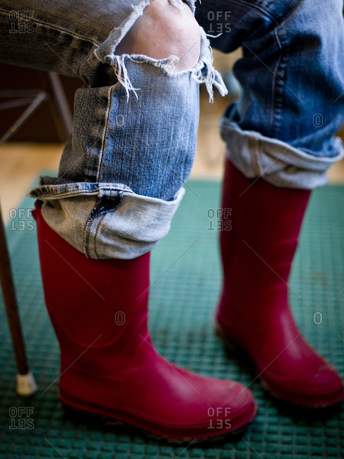 Red rubber boots and torn jeans