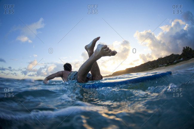 A young man paddles by Monster Mush, on the north shore of Oahu, Hawaii