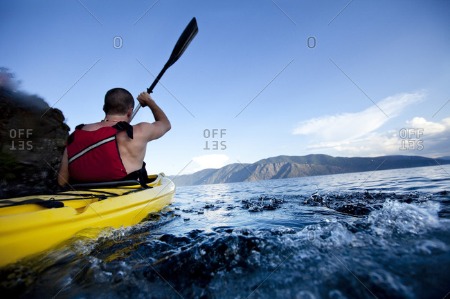 Young man paddles yellow kayak on lake
