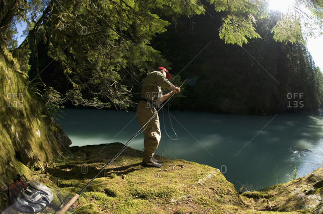 A man prepares his fly rod while fly fishing in Squamish, British Columbia