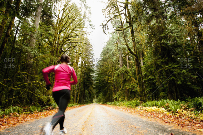 A female jogging down a road next to tall trees covered in moss