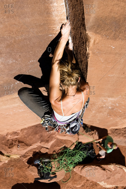 A female rock climber climbs Ruby's Cafe, a classic 513 rated climb in Indian Creek, Utah