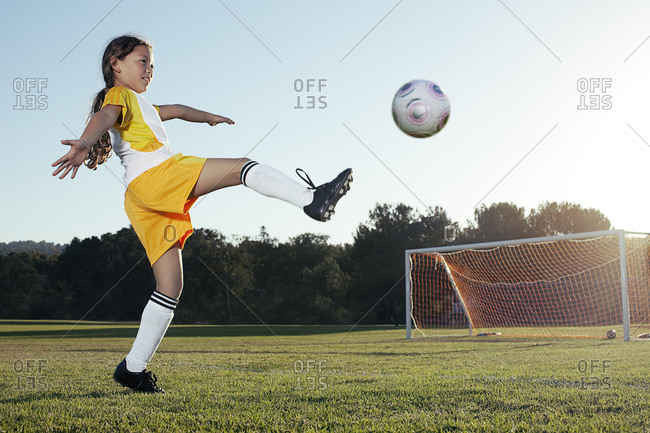 A young girl playing soccer on a soccer field in Los Angeles, California